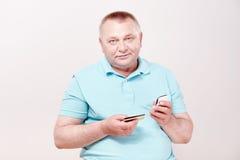 Pensionär med telefonen och kortet Arkivbild
