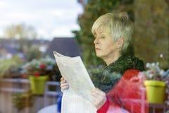 Pensionär med tidningen Arkivbilder
