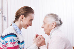 Pensionär- och anhörigvårdareinnehavhänder hemma arkivfoton