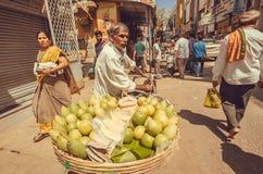 Pensionär på stadsmarknadsgatan som säljer nya guavafrukter i folkmassan av upptaget folk Royaltyfria Foton