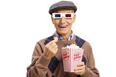 Pensionär som bär ett par av exponeringsglas 3D och har popcorn Royaltyfri Fotografi