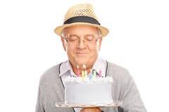Pensionär som blåser stearinljus på en födelsedagkaka Royaltyfri Bild