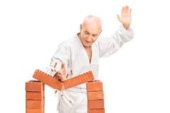 Pensionär som bryter en tegelsten med hans kala hand fotografering för bildbyråer