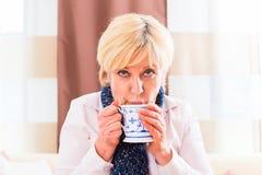 Pensionär som dricker te för att kurera hennes influensa Arkivfoton