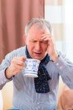 Pensionär som dricker te för att kurera influensa Royaltyfria Bilder