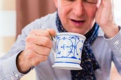 Pensionär som dricker te för att kurera influensa Fotografering för Bildbyråer