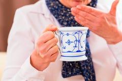 Pensionär som dricker te för att kurera influensa Royaltyfri Bild
