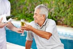 Pensionär som får champagne från uppassare Royaltyfri Bild