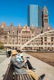 Pensionär som framme vilar av gammalt stadshus i Toronto arkivfoto