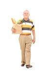 Pensionär som går med en påse av livsmedel Arkivbilder