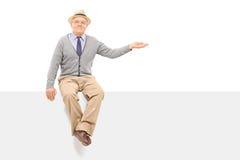 Pensionär som gör en gest med handen som placeras på en tom panel Arkivbilder