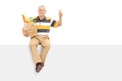 Pensionär som ger en tumme som placeras upp på en panel Arkivfoto