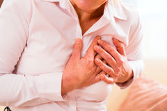 Pensionär som har hjärtinfarkt hemma Royaltyfria Bilder