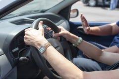Pensionär som lär att köra en bil med en körningsinstruktör Fotografering för Bildbyråer