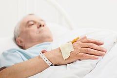 Pensionär som ligger i en sjukhussäng med iv-uppsättningen på hans hand royaltyfria bilder