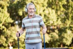 Pensionär som lyssnar till musik, medan gå i parkera royaltyfri bild