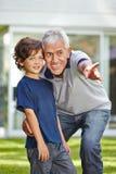 Pensionär som pekar med fingret för barnbarn Arkivbilder