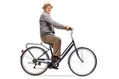 Pensionär som rider en cykel och ser kameran royaltyfri bild