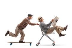 Pensionär som rider en longboard och skjuter en shoppingvagn med anoth arkivfoton