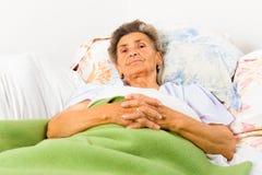 Pensionär som säger böner Royaltyfria Bilder