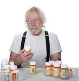 Pensionär som ser en flaska av preventivpillerar Arkivbild