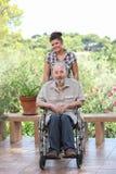 Pensionär som skjuts i rullstol Royaltyfria Foton