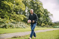 Pensionär som spelar fotboll med grandkidsna Royaltyfria Bilder