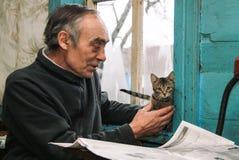 Pensionär som spelar med kattungar Royaltyfri Foto