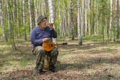Pensionär som spelar musik i björkskog Royaltyfria Bilder