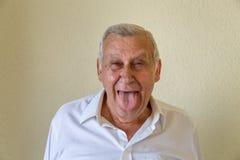 Pensionär som ut klibbar hans tunga Arkivbild