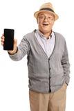 Pensionär som visar en telefon till kameran och le Arkivbild
