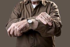 Pensionär som visar hans klockarmbandklocka arkivfoto