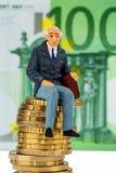 Pensionäre, die auf Stapel des Geldes sitzen Stockfoto