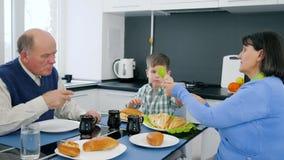 Pensionären barn äter bageriprodukter med farfadern och farmodern i kök stock video