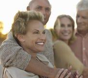 Pensionären kopplar ihop att koppla av tillsammans på stranden royaltyfri fotografi