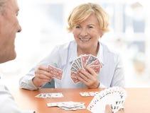 Pensionären kopplar ihop att leka ett kortspel Royaltyfri Bild