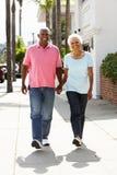 Pensionären kopplar ihop den gå Along gatan tillsammans Arkivfoto
