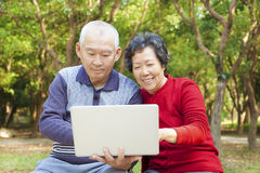 Pensionären kopplar ihop med bärbar dator Arkivbilder