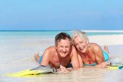 Pensionären kopplar ihop med Snorkels som tycker om strandferie Royaltyfri Foto