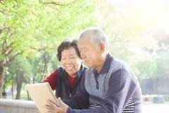 Pensionären kopplar ihop med tabletPC arkivbilder
