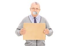 Pensionären med kanalen tejpade munnen som rymmer ett tomt tecken Royaltyfri Bild