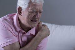 Pensionären med skuldran smärtar royaltyfri fotografi