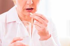 Pensionären medicate med hemmastadda preventivpillerar Arkivbild