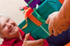 Pensionären sitter och får eller ger closeupen för många presents Arkivfoto