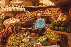 Pensionären som säljer frukter, ingefäran, kokosnötter och grönsaker för kunder på bönder marknadsför Arkivfoto