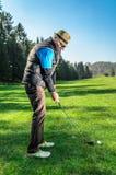 Pensionären spelar golf arkivbilder