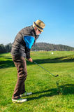 Pensionären spelar golf royaltyfria bilder