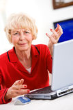 Pensionärer: Hög kvinna som är förvirrad vid bärbara datorn Royaltyfria Bilder