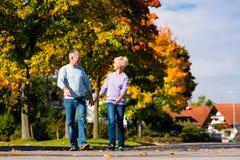 Pensionärer i gå hand för höst eller för fall - in - hand royaltyfria foton
