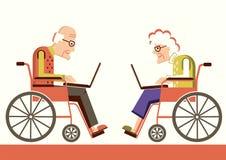 Pensionärer i rullstolar med bärbara datorer Royaltyfri Foto